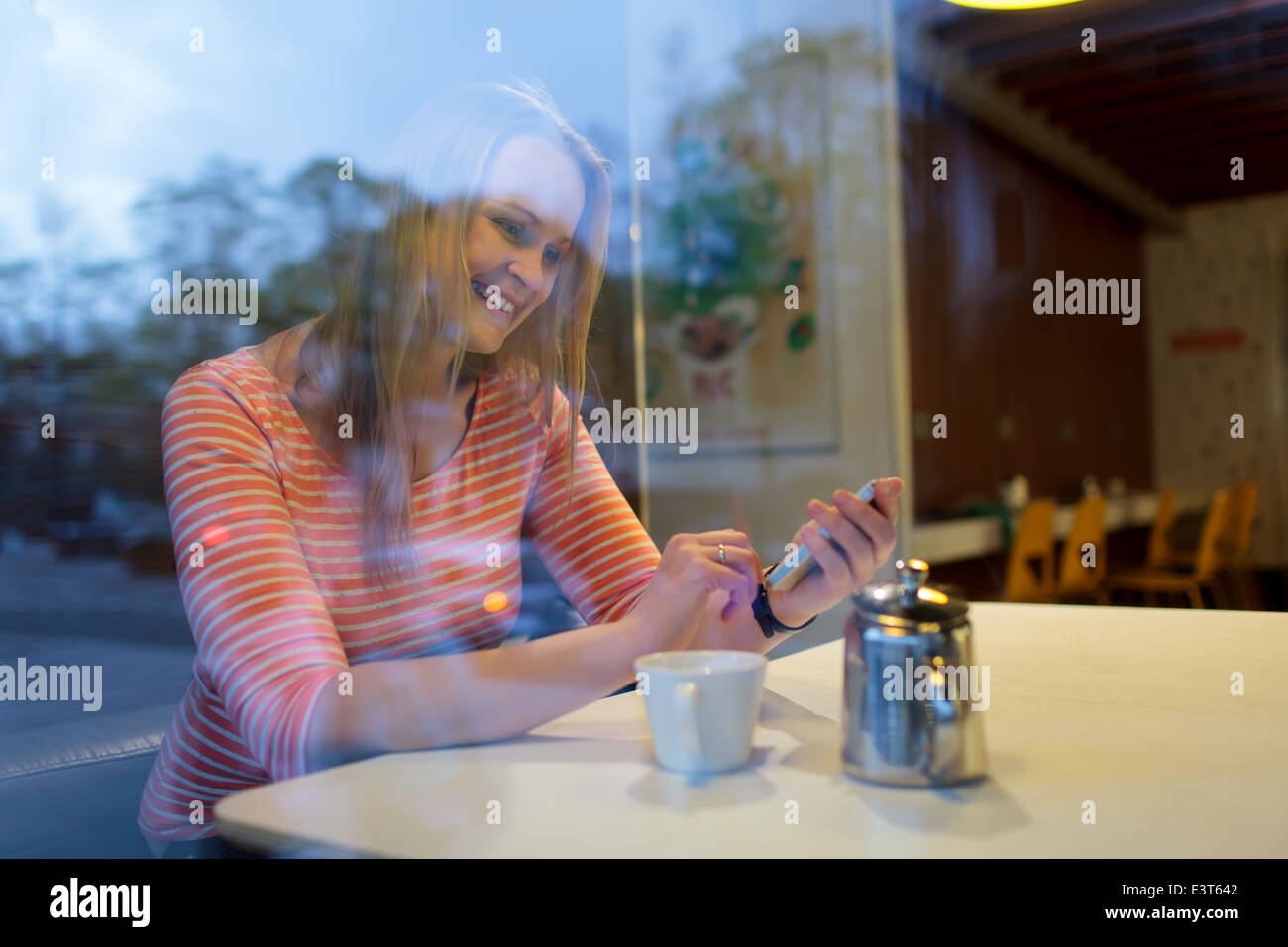 Young woman using a mobile phone in a cafeteria - Stock Image