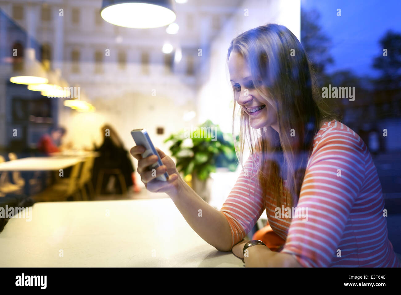 Young woman sitting in a restaurant using a mobile - Stock Image
