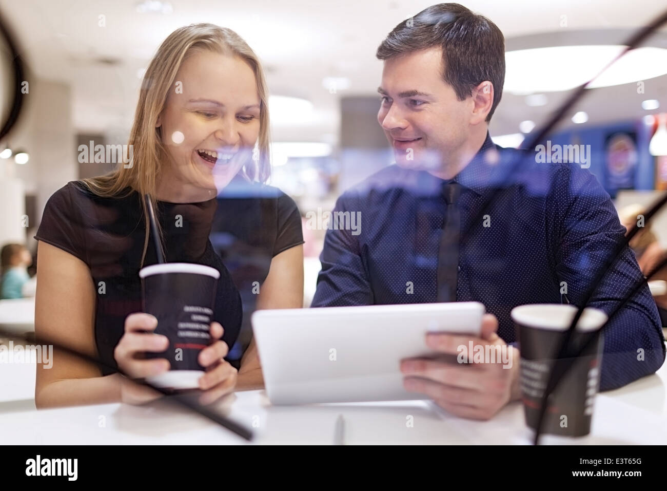 Woman laughs as man shows tablet - Stock Image