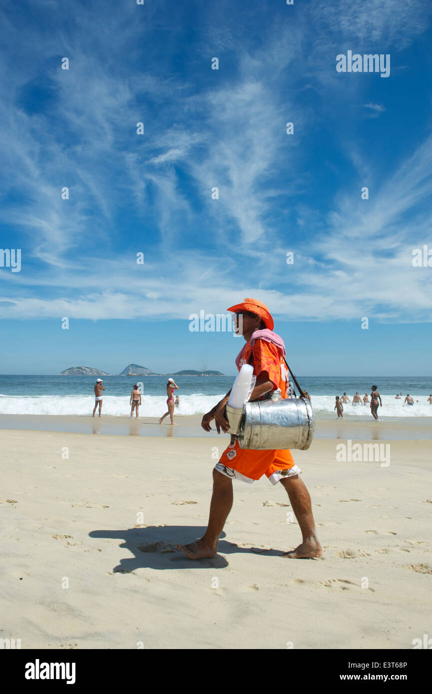 RIO DE JANEIRO, BRAZIL - MARCH 10, 2013: Brazilian beach vendor selling South American mate tea walks in uniform - Stock Image