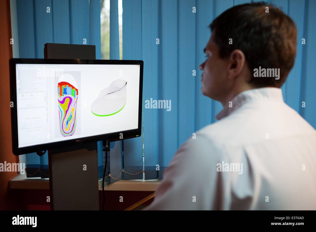 Orthopaedist at work with digital footstep model - Stock Image