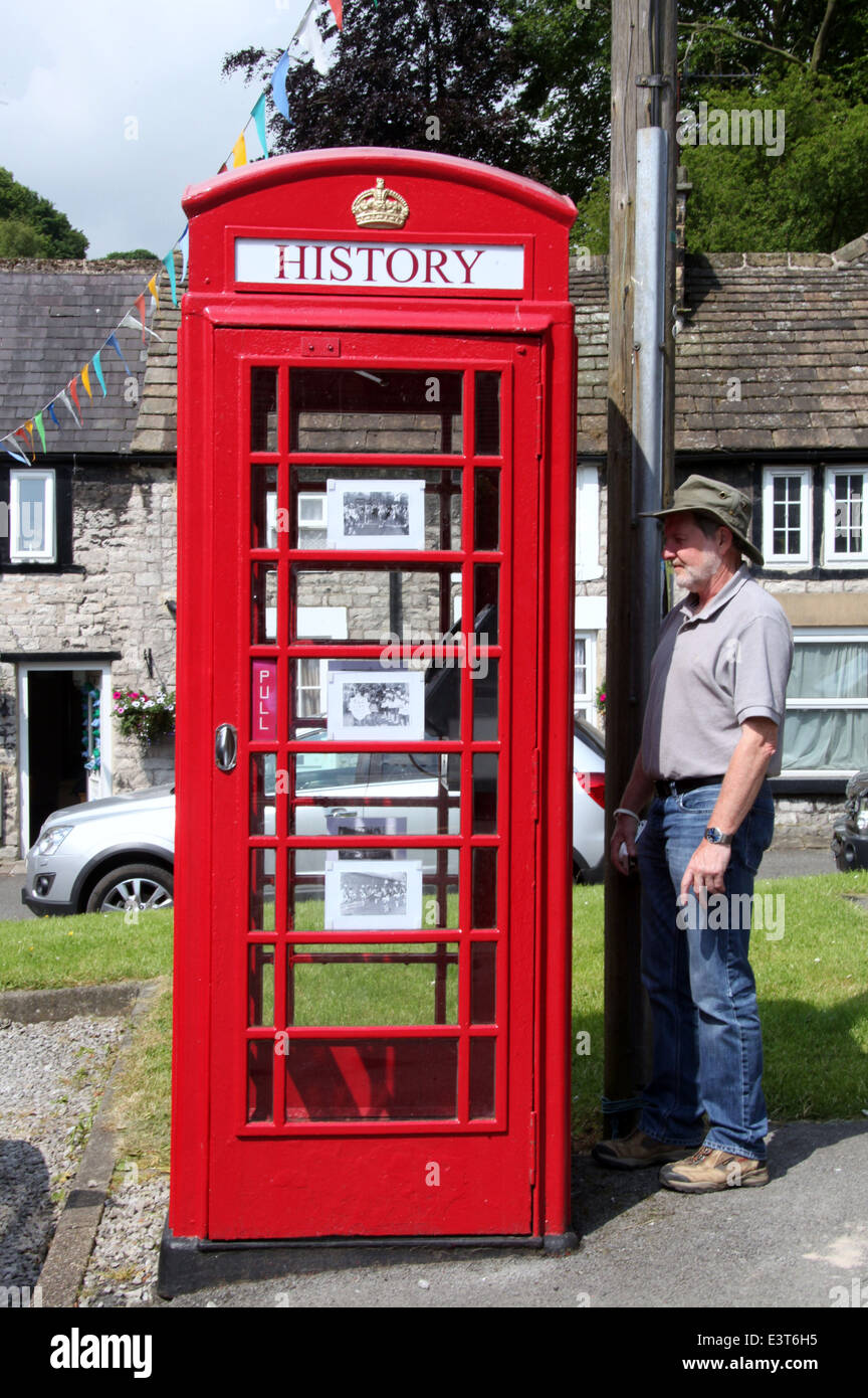 Tourist reading a poem on a  converted phone box in the Derbyshire Village of Tideswell - Stock Image