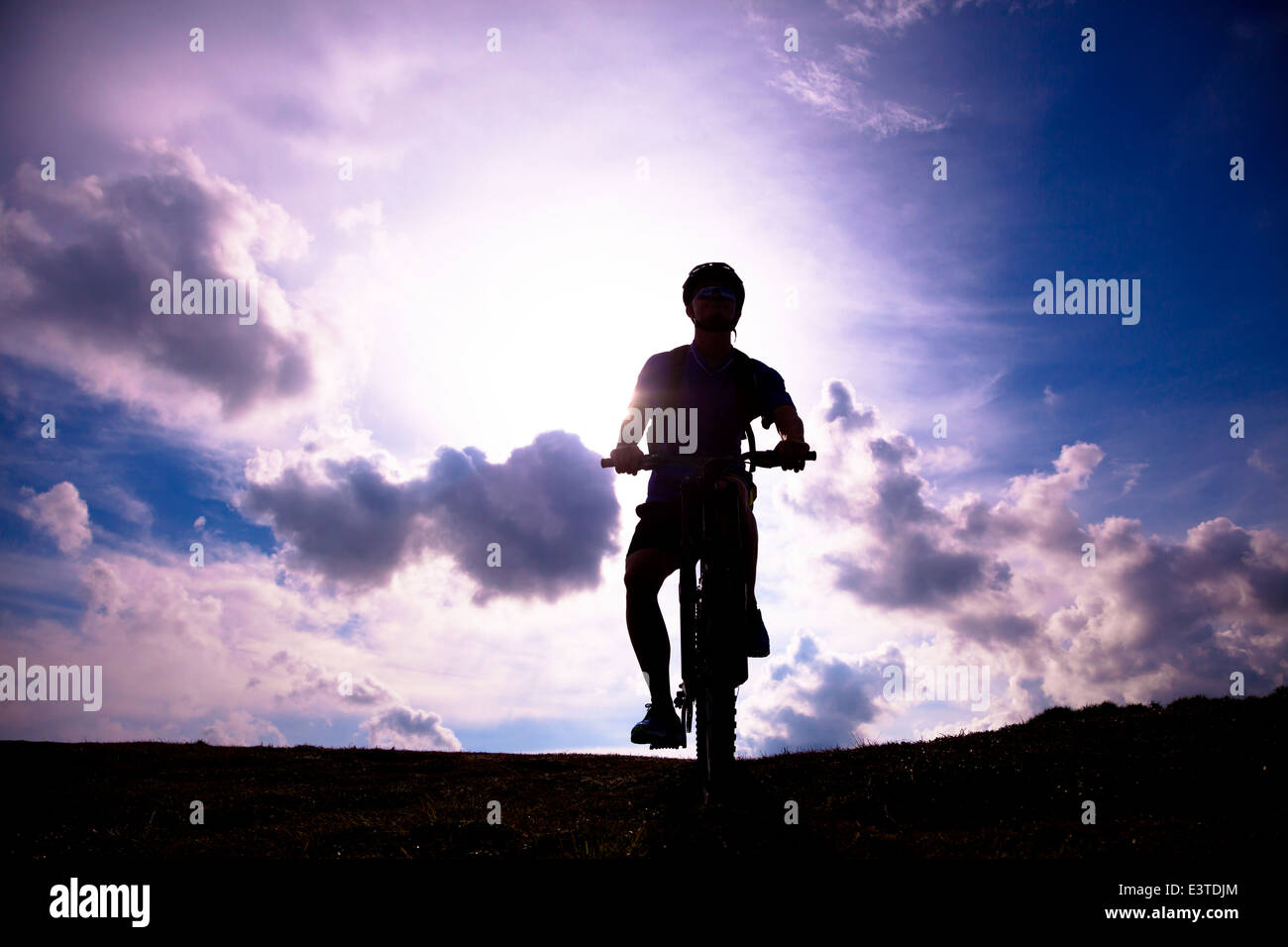 mountain bicycle rider on the hill with sunrise background - Stock Image