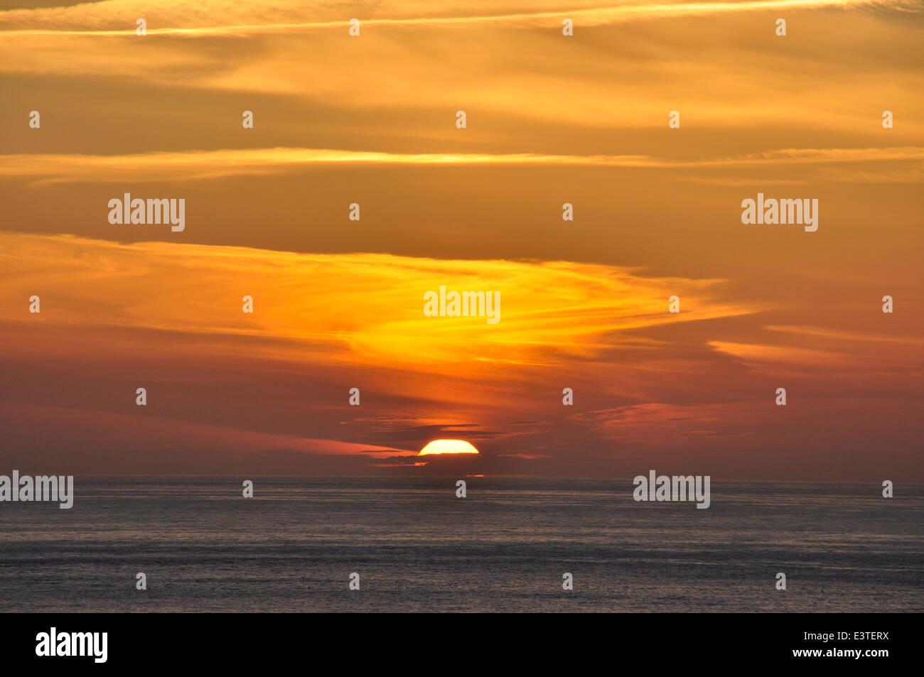 Cornwall - North Coast path - sunset over the sea - orange - red - gold - sky over a dark reflective sea - Stock Image