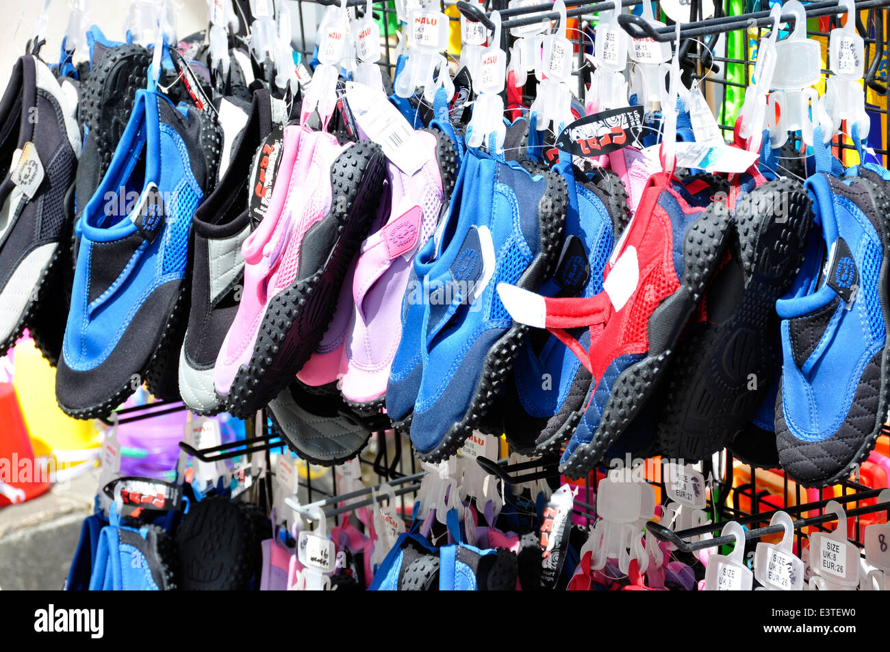 Colourful row of beach shoes - seaside sales display - bright sunlight - summertime - Stock Image