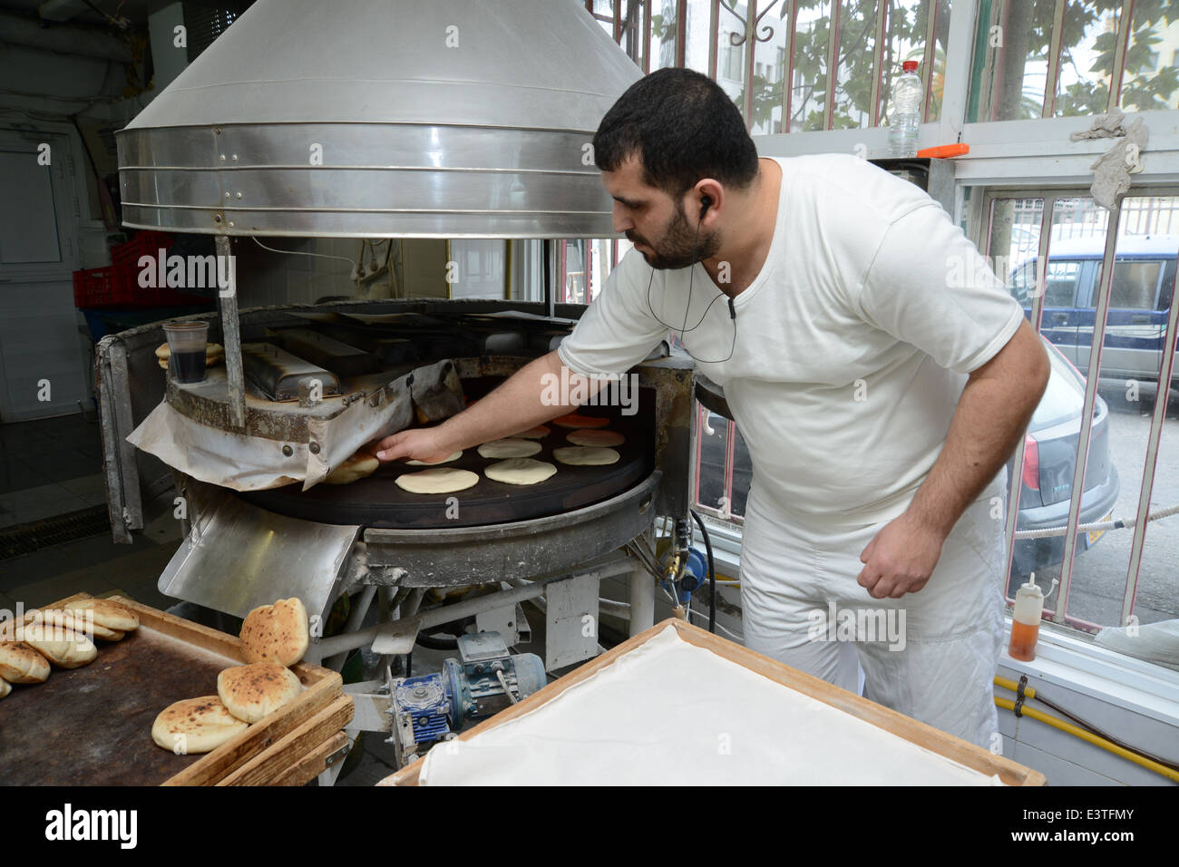 Pita Bakery. The baker removes the pita from the oven - Stock Image