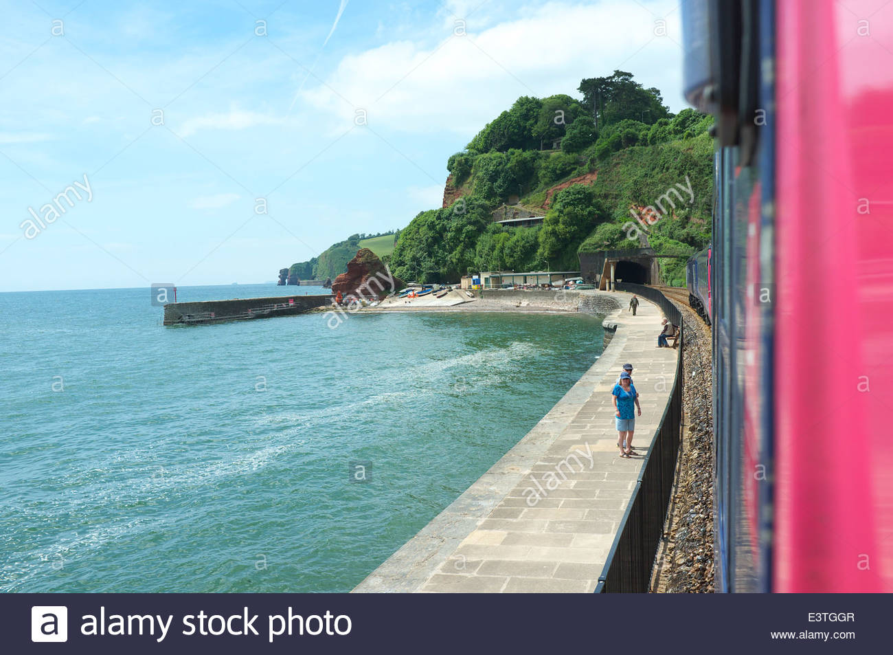 A London Paddington to Plymouth train passes through Dawlish, along the famous seawall route in south Devon, UK. - Stock Image