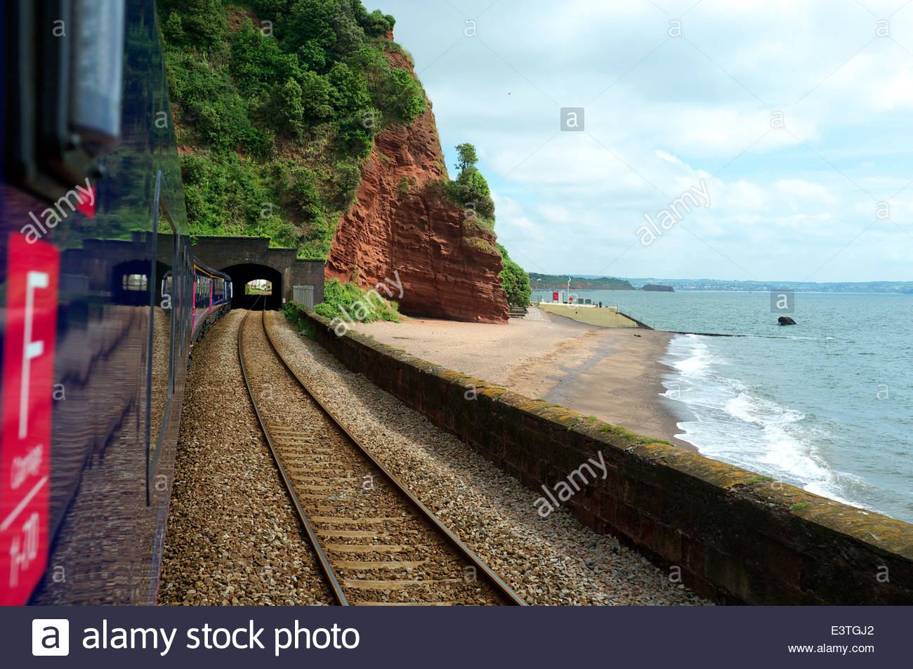 A First Great Western service to London Paddington about to enter Kennaway Tunnel and pass through Dawlish town, - Stock Image
