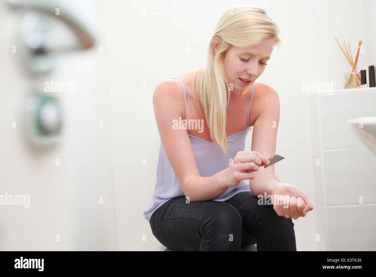 Teenage Girl Self Harming With Knife Blade - Stock Image