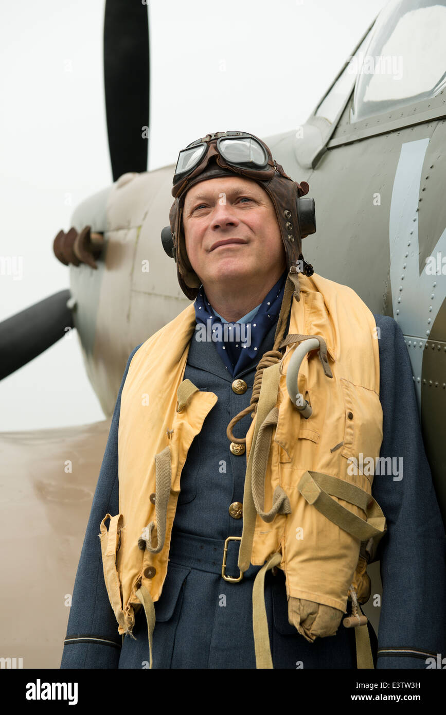 WW2 RAF pilot wearing his Mae West life jacket, stands at the ready beside his Spitfire fighter aircraft. - Stock Image