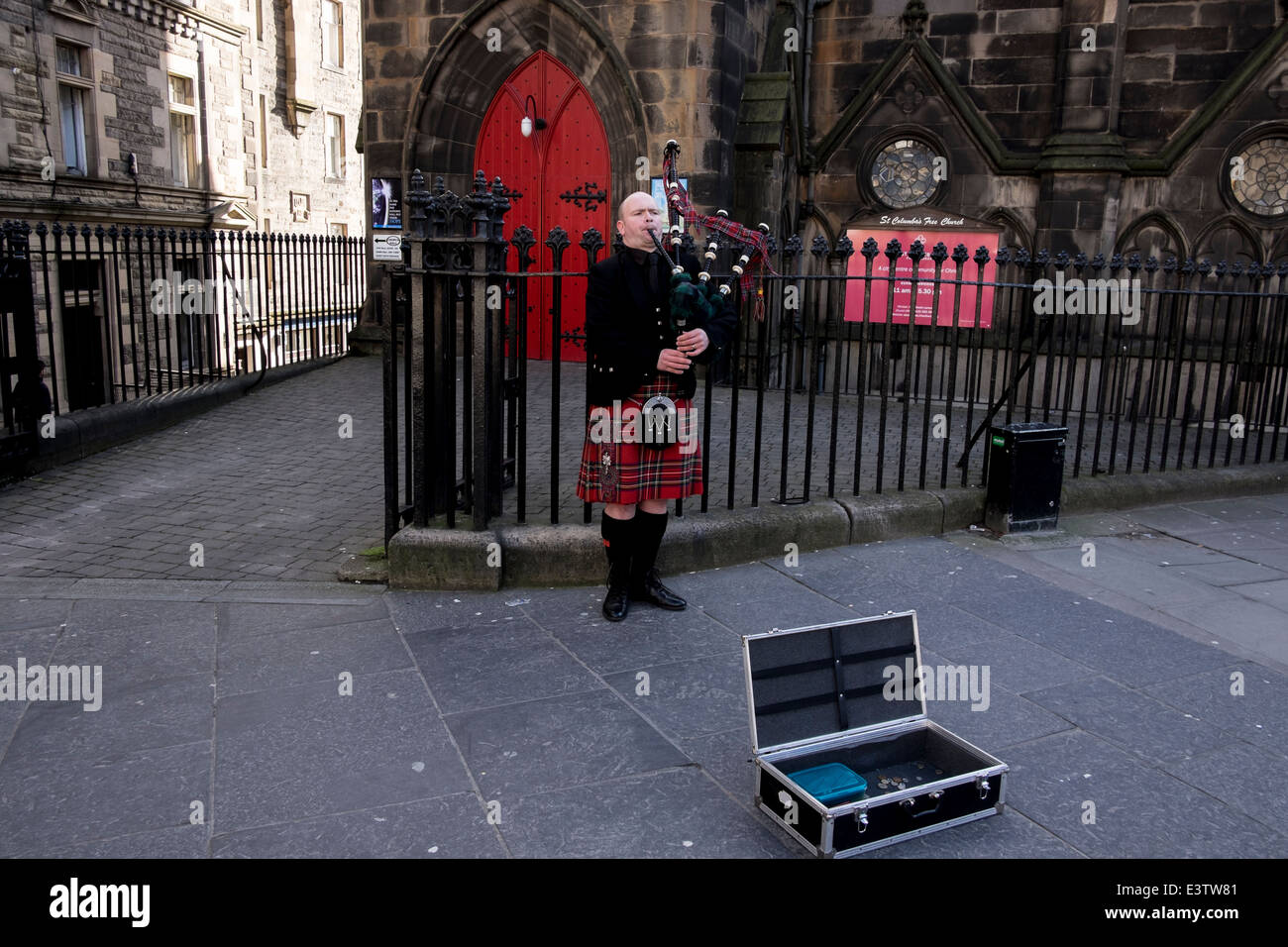 A man in traditional suit plays bagpipe in Edinburgh, Scotland - Stock Image