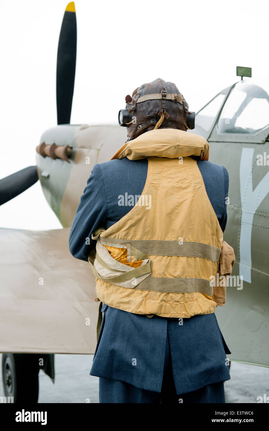 WW2 RAF pilot, wearing his Mae West life jacket stands beside his Spitfire fighter aircraft, waiting to scramble. - Stock Image