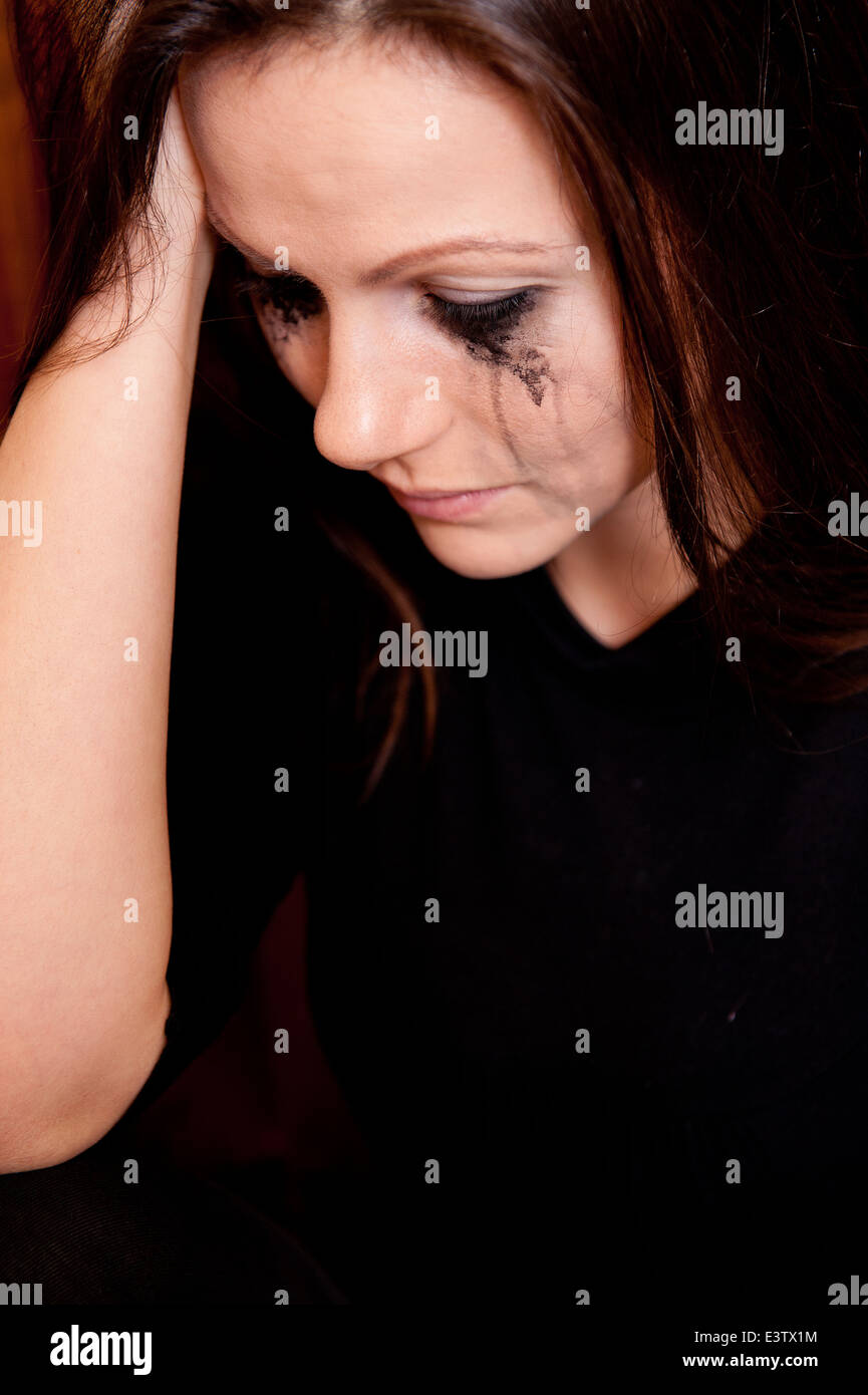 Tearful young woman with her make-up running down her face. - Stock Image