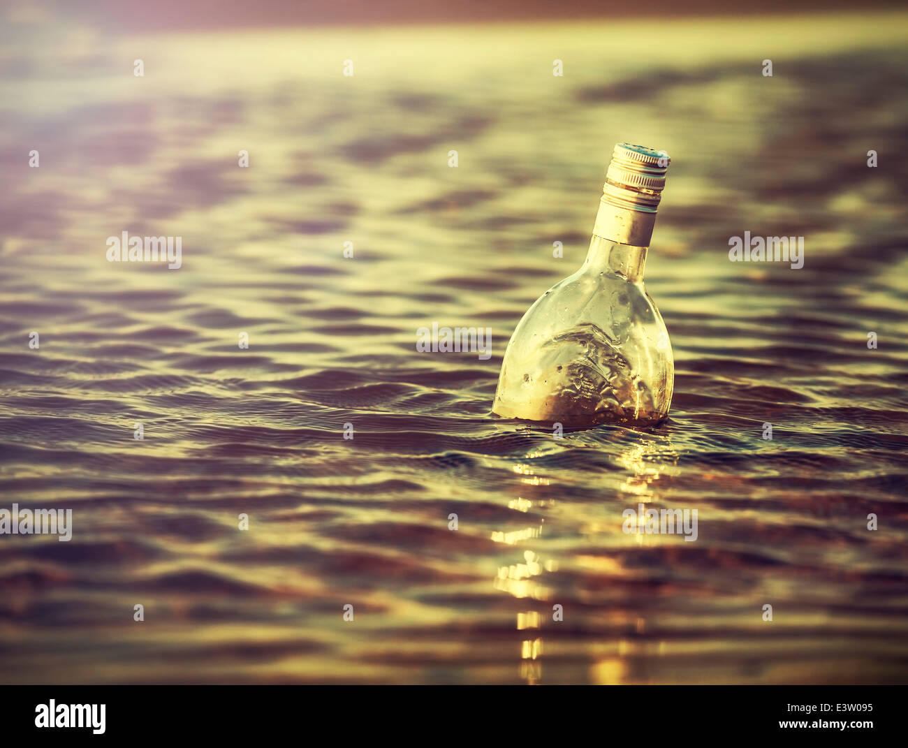 Bottle in water at sunset, retro instagram vintage effect. - Stock Image