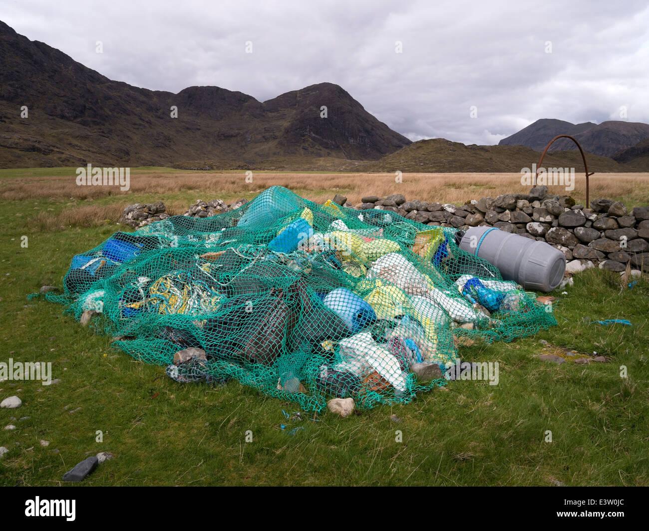 Collection of beach rubbish (flotsam and jetsam) under old fishing net at Camasunary Bay, Isle of Skye, Scotland, - Stock Image