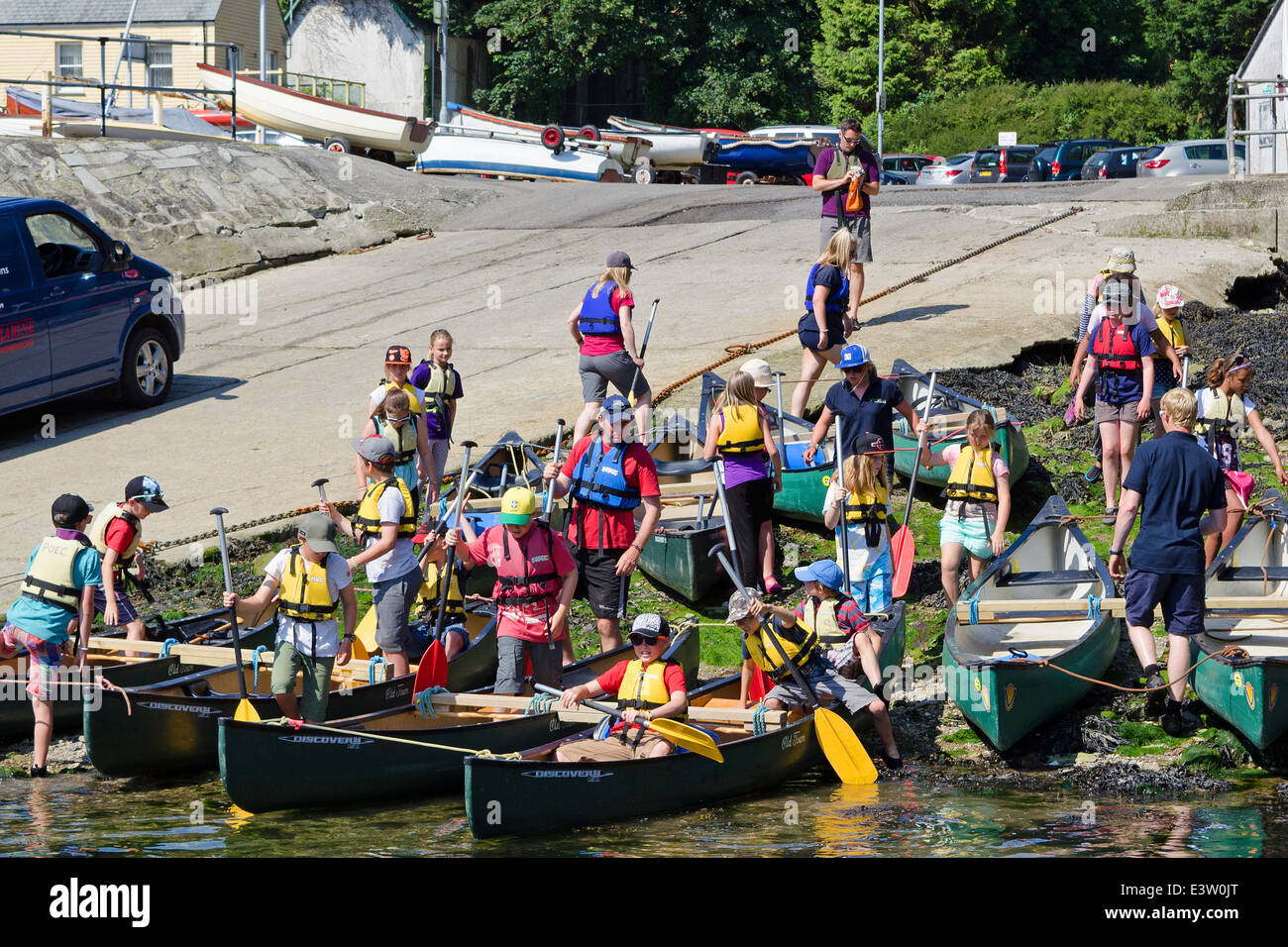 school children prepare to have canoe lessons on the river fowey in cornwall, uk - Stock Image