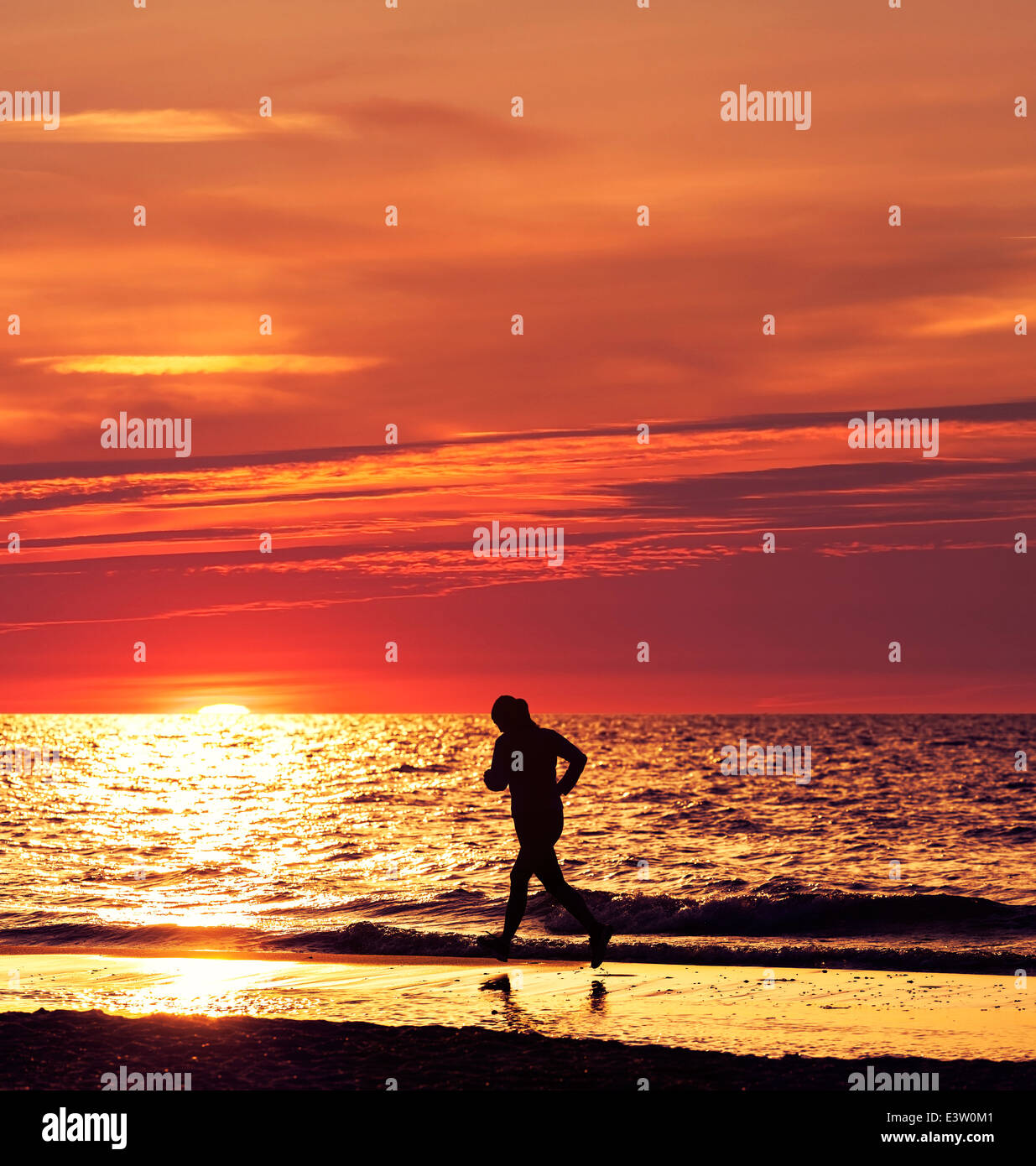 Woman running at beautiful sunset in the beach. - Stock Image