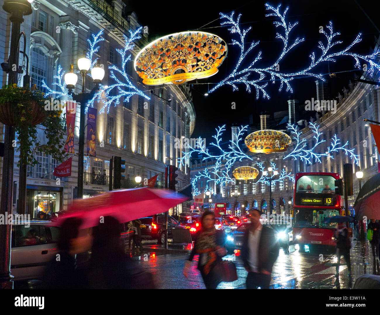Busy scene of Christmas shoppers, traffic and umbrellas in a rain swept Regent Street with Christmas lights behind Stock Photo