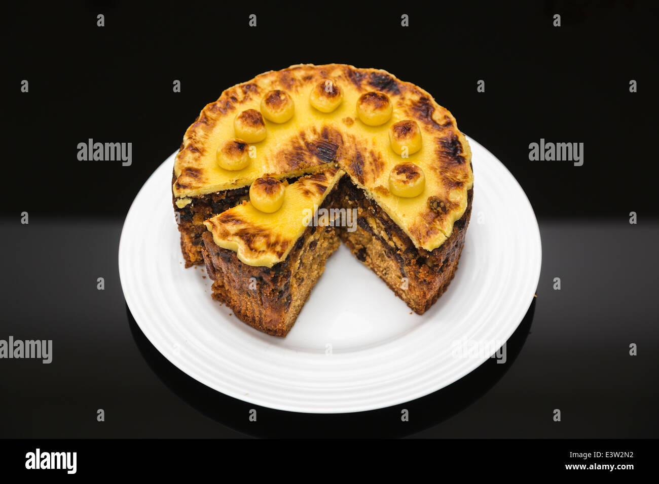 Traditional home baked round Easter simnel cake, topped with marzipan, sliced, on a circular white plate with black Stock Photo