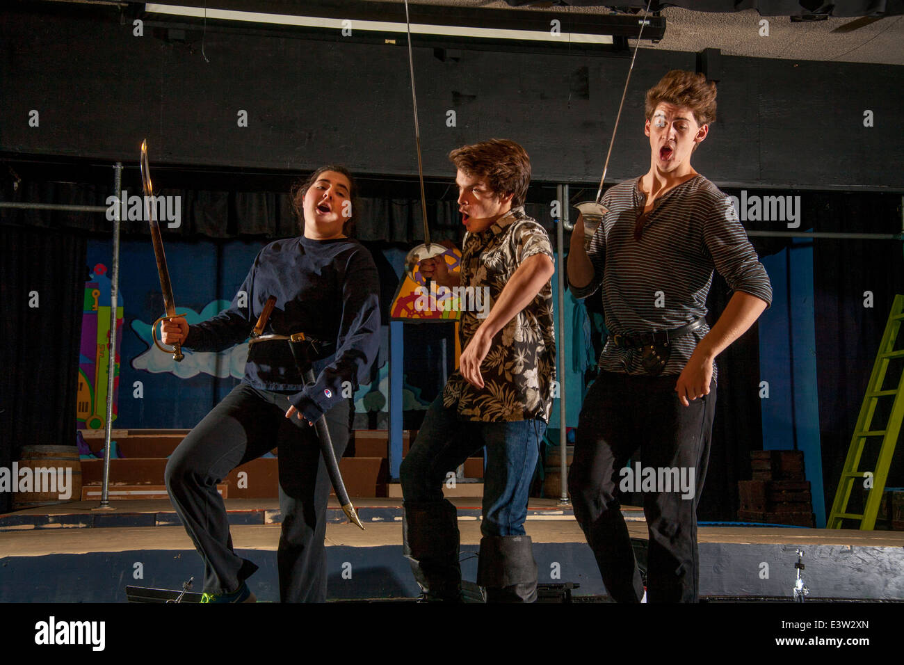 High school student cast members brandish swords and shout during rehearsal of Gilbert & Sullivan's 'Pirates - Stock Image