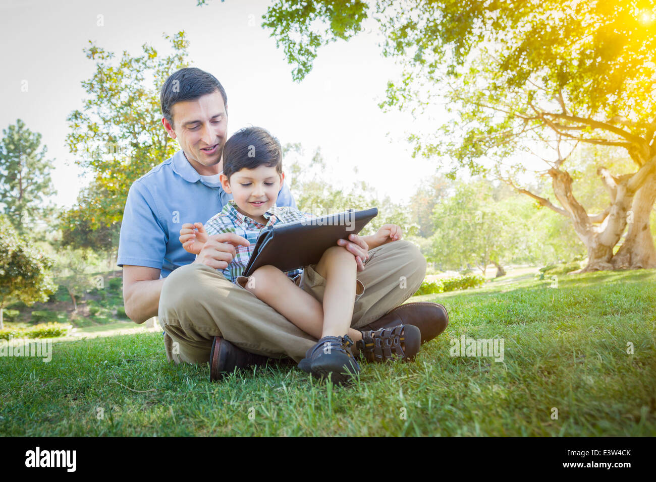 Handsome Mixed Race Father and Son Playing on a Computer Tablet Outside. - Stock Image