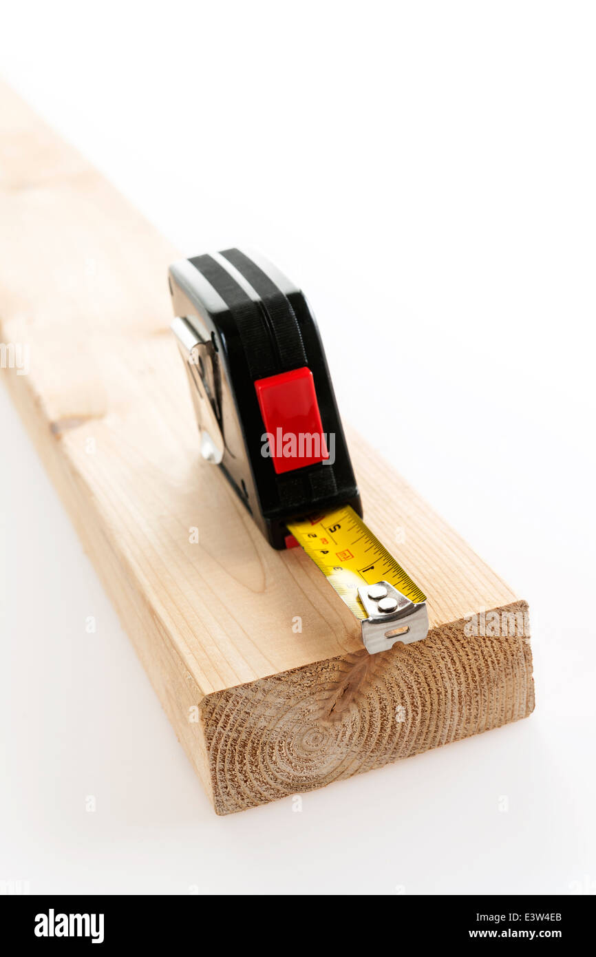 Metal imperial metric tape measure measuring two by four lumber on white background - Stock Image