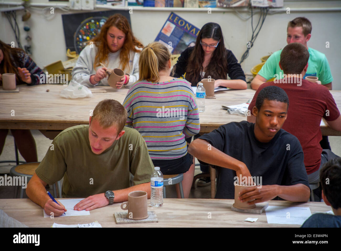 Multiracial high school pottery students in San Clemente, CA, work on their class assignment, a clay mug Stock Photo