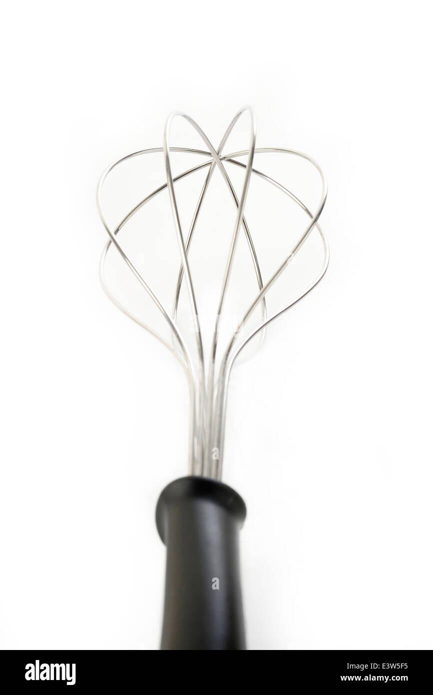kitchen whisk on white background - Stock Image