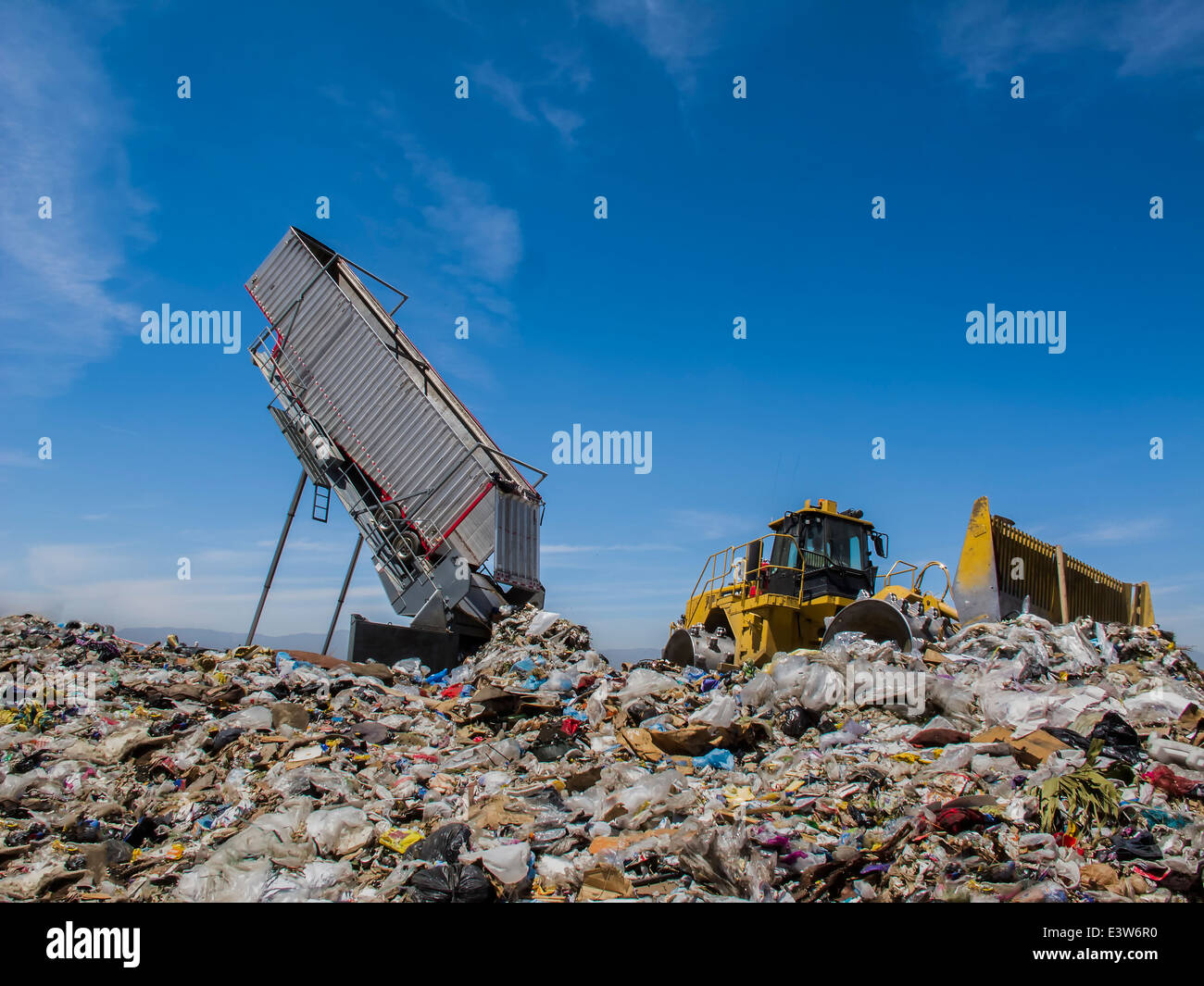 Modern hydraulic disposer empties a complete trailer, while bulldozer manages landfill. - Stock Image