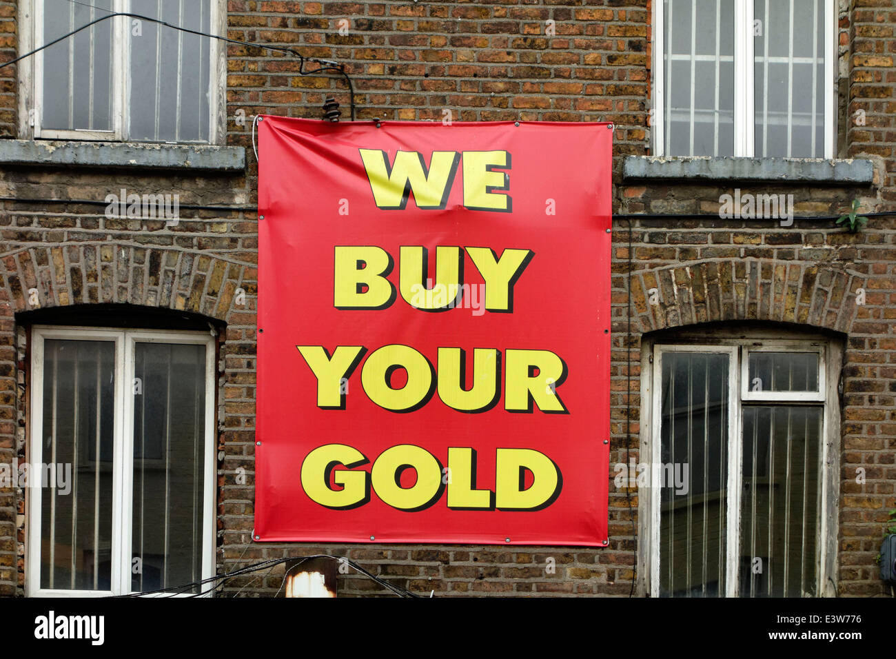 We buy your gold sign hanging on brick wall, Dublin, Republic of Ireland, Europe. - Stock Image