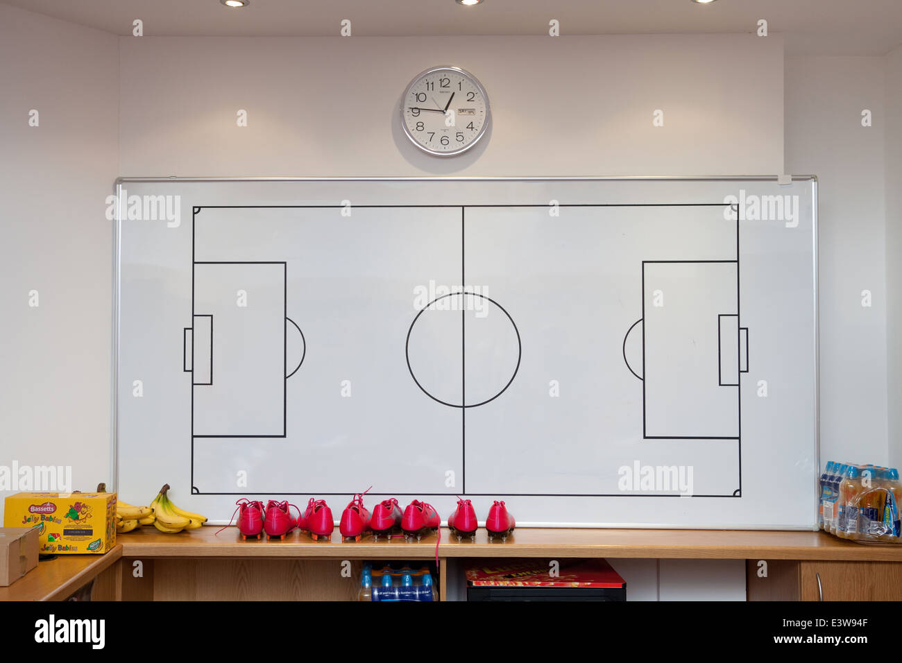A white board with a football pitch marked on it in a dressing room - Stock Image