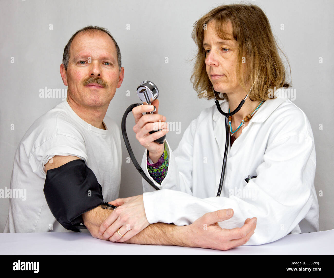 Doctor checks blood pressure of a patient - Stock Image