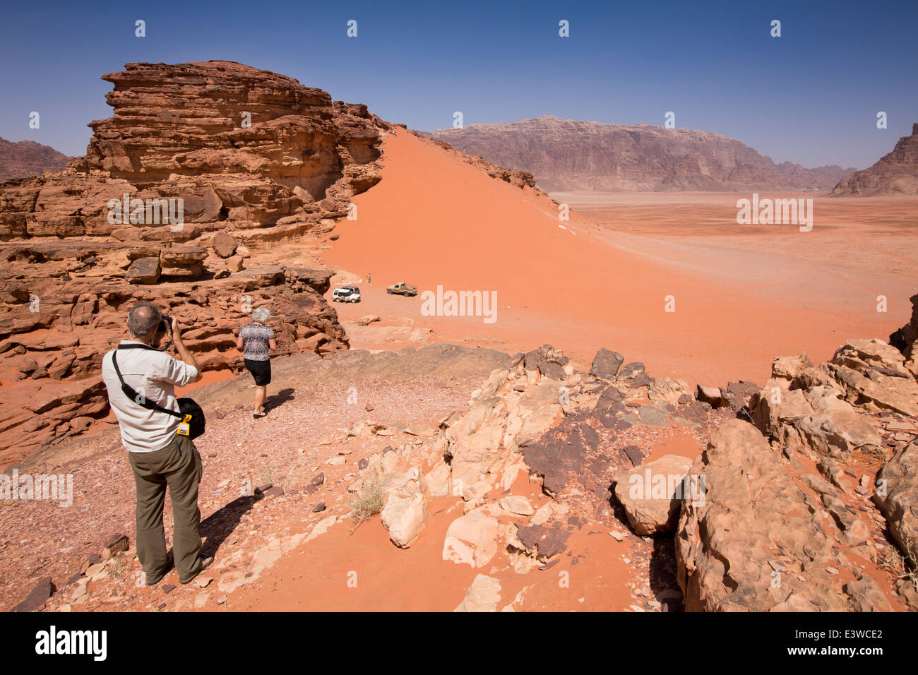 Jordan, Wadi Rum, western tourists viewing red sand dunes from rocky outcrop - Stock Image