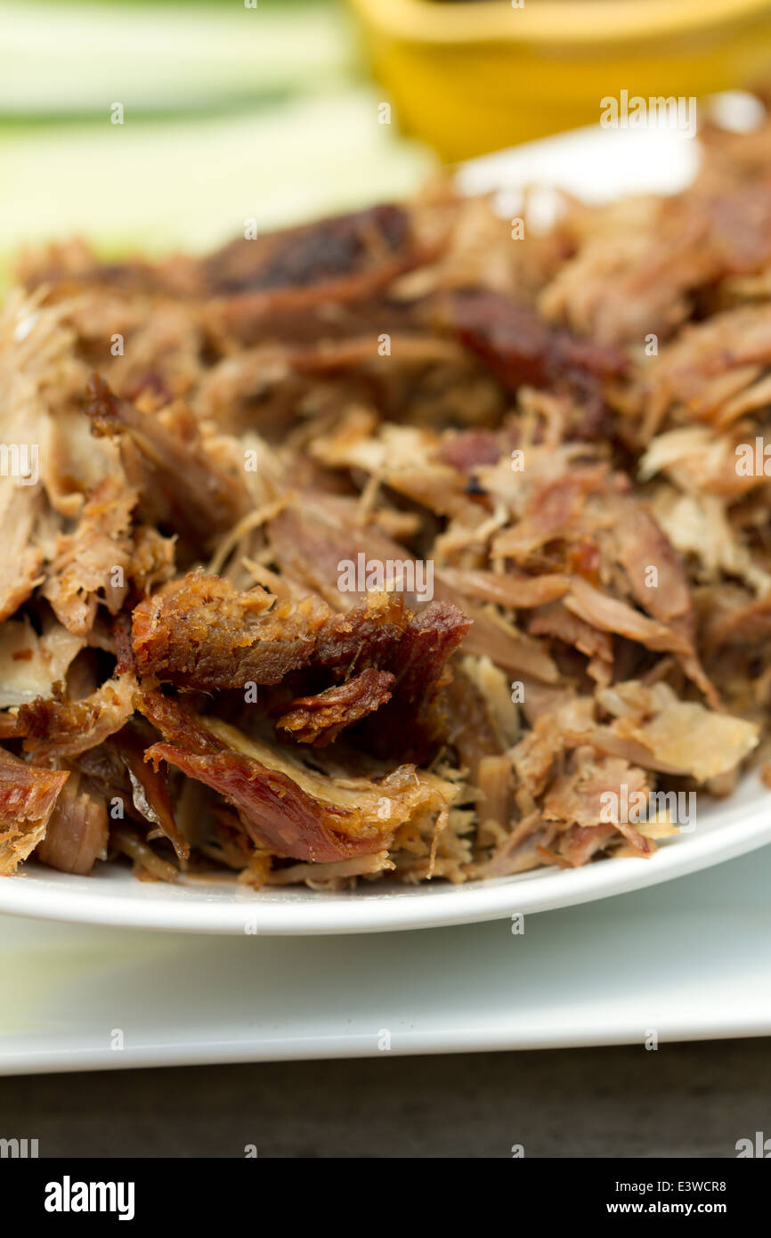 Crispy aromatic duck, shredded on a platter with cucumber and spring onion strips, and hoisin sauce - Stock Image
