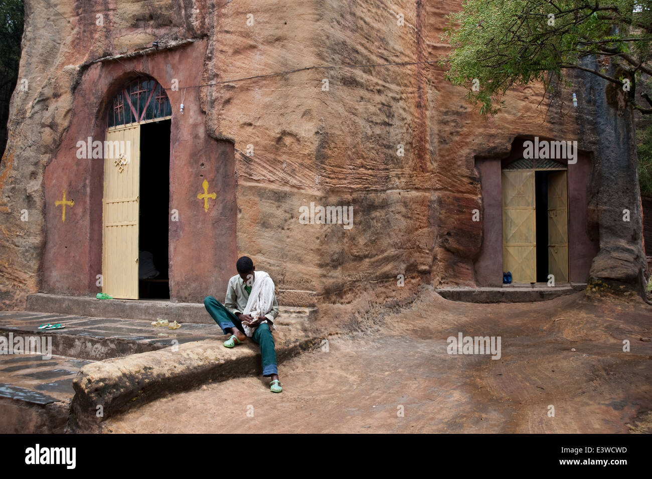 Religious student reading the Bible in front of a rock hewn church. He is orthodox christian ( Ethiopia) - Stock Image