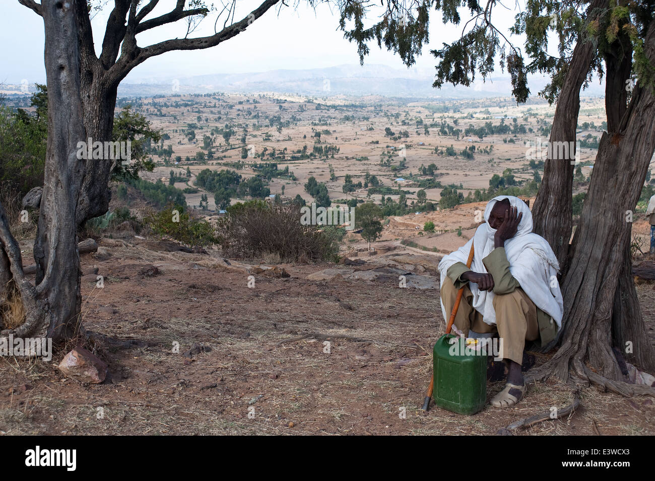 Man sitting under a tree. In the background, a landscape of hills ( Ethiopia) - Stock Image