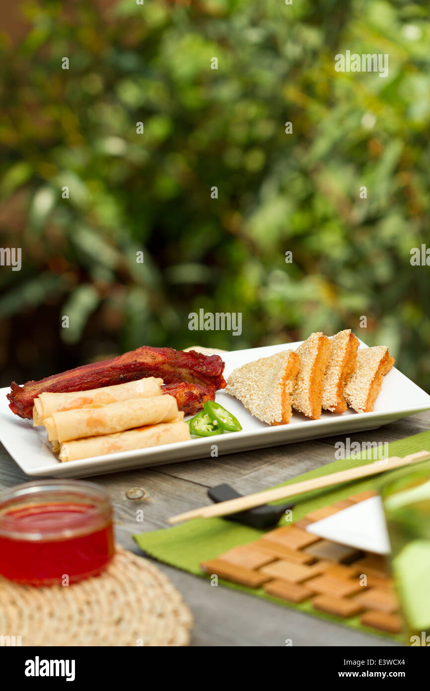 Chinese food appetizers on a platter outside, including spring rolls, ribs and sesame prawn on toast - Stock Image