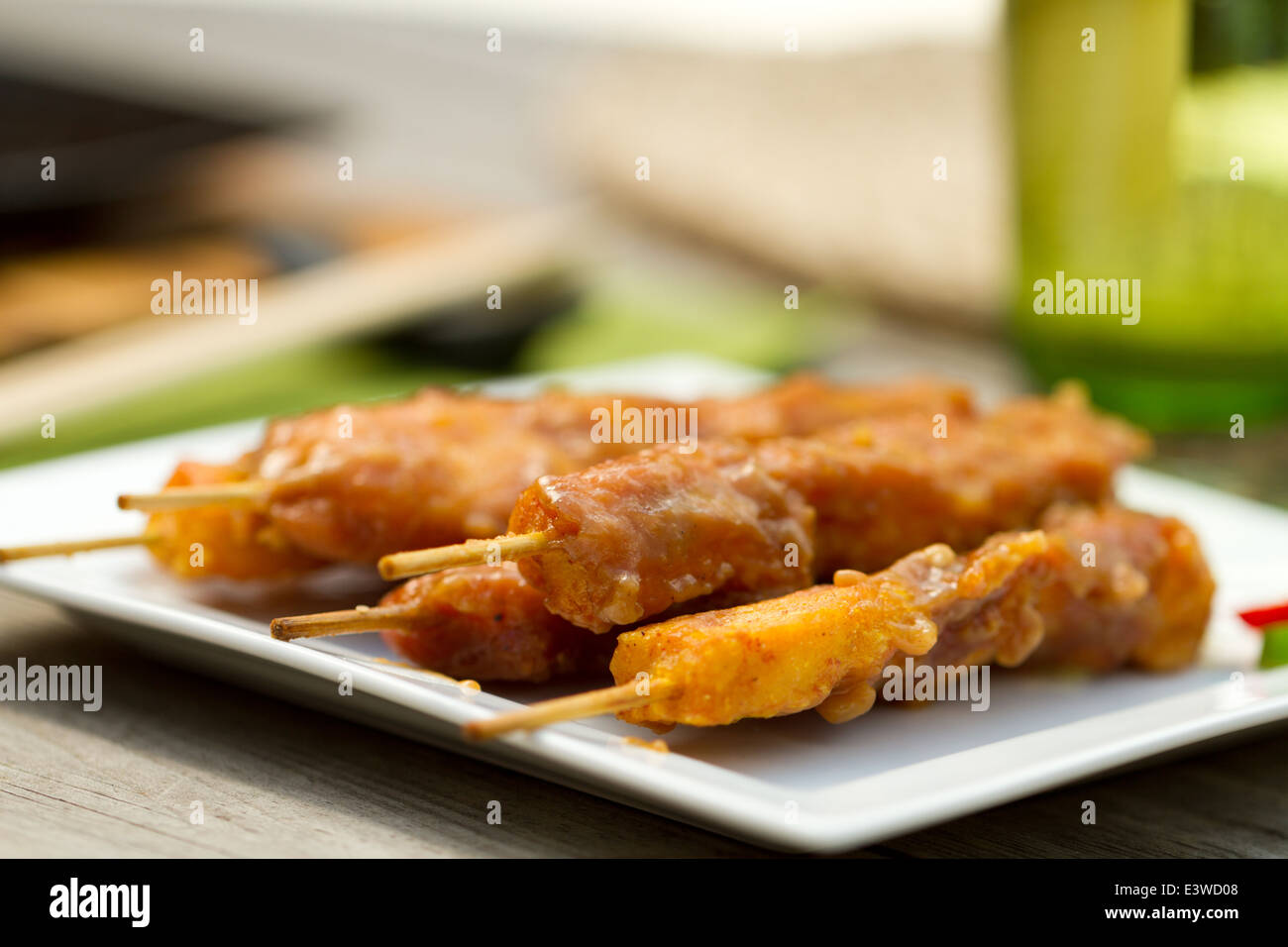 Satay chicken on skewers on a square white plate outside - Stock Image