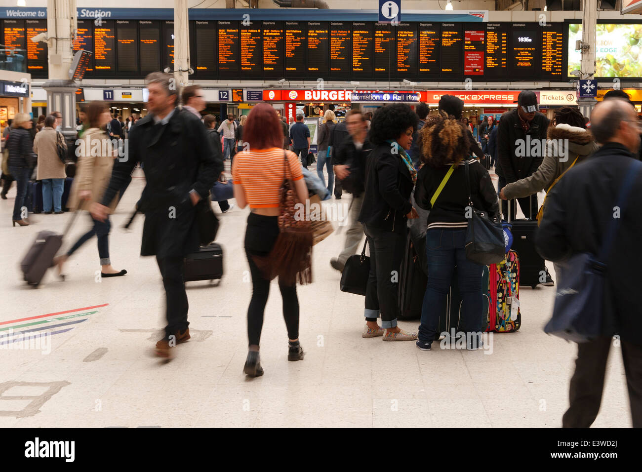 Group of people chatting at Victoria Station in rush hour. Passers buy showing motion blur. - Stock Image