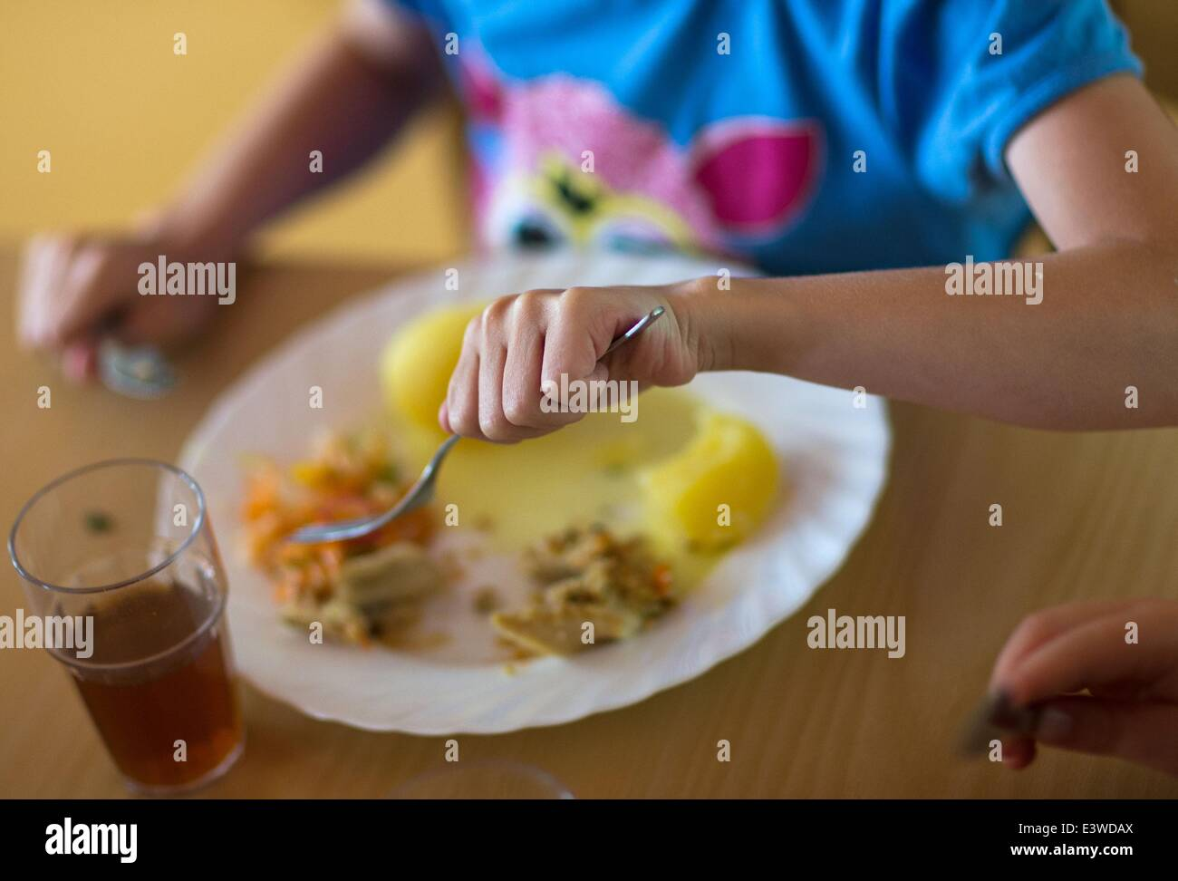 Wismar, Germany. 19th June, 2014. Nursery child Romina eats her lunch from her plate with a knife and fork at the Stock Photo