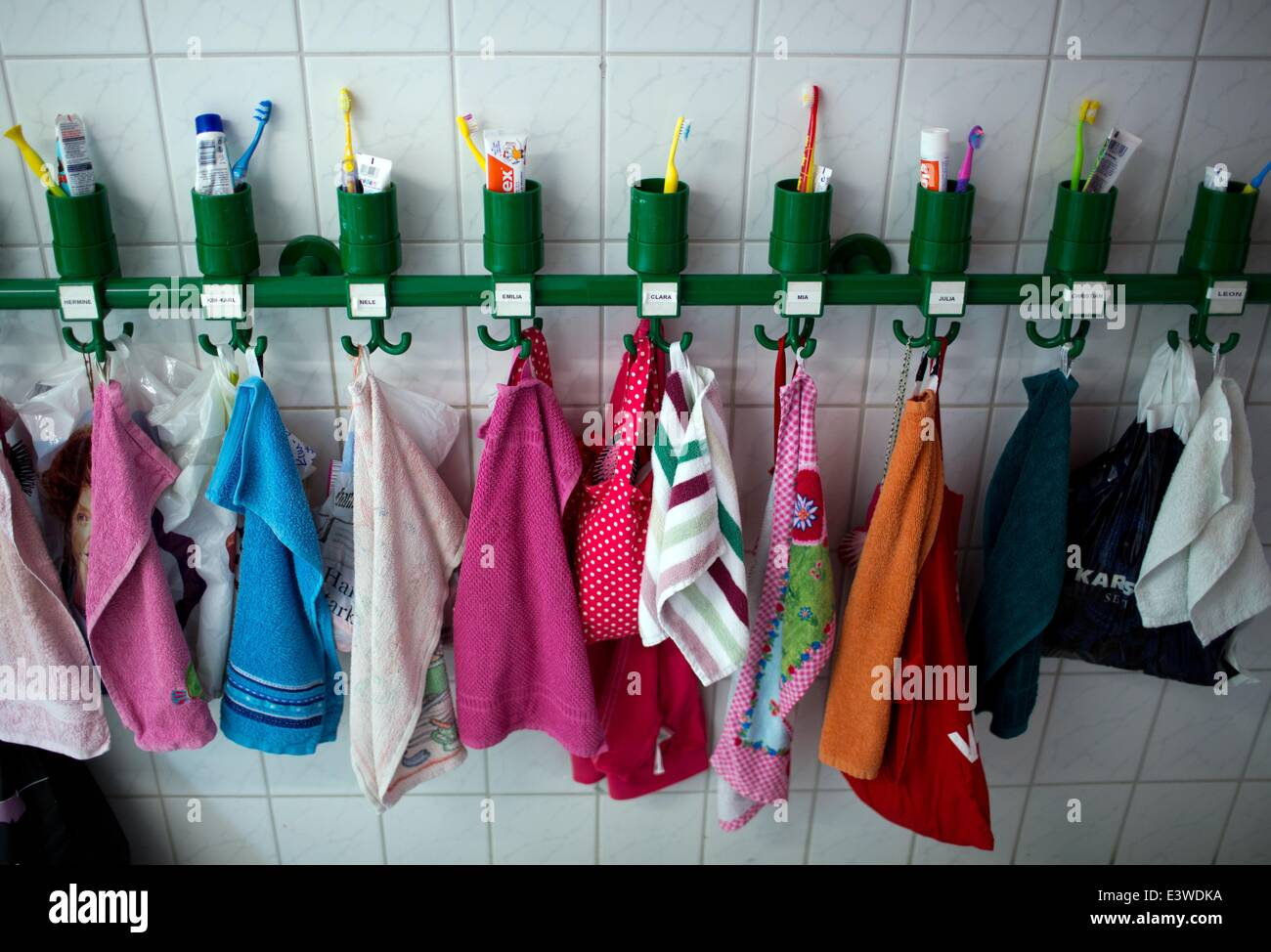 Wismar, Germany. 19th June, 2014. Colourful towels and toothbrush tumblers stand on a shelf in the washing room Stock Photo