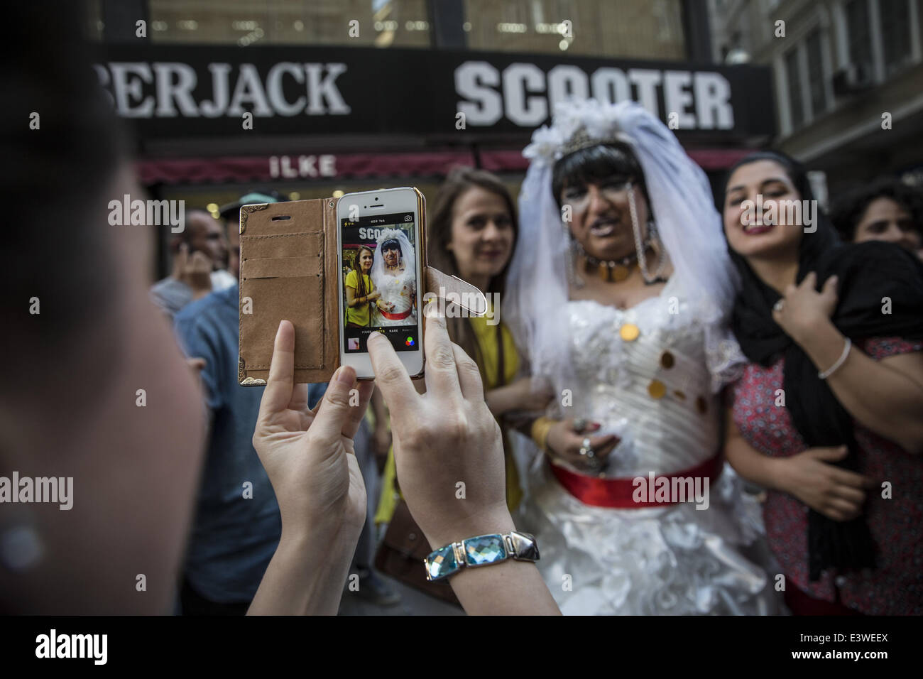 Istanbul, Turkey. 29th June, 2014. An Iranian woman poses for a photo with a trans person dressed as a bride during - Stock Image