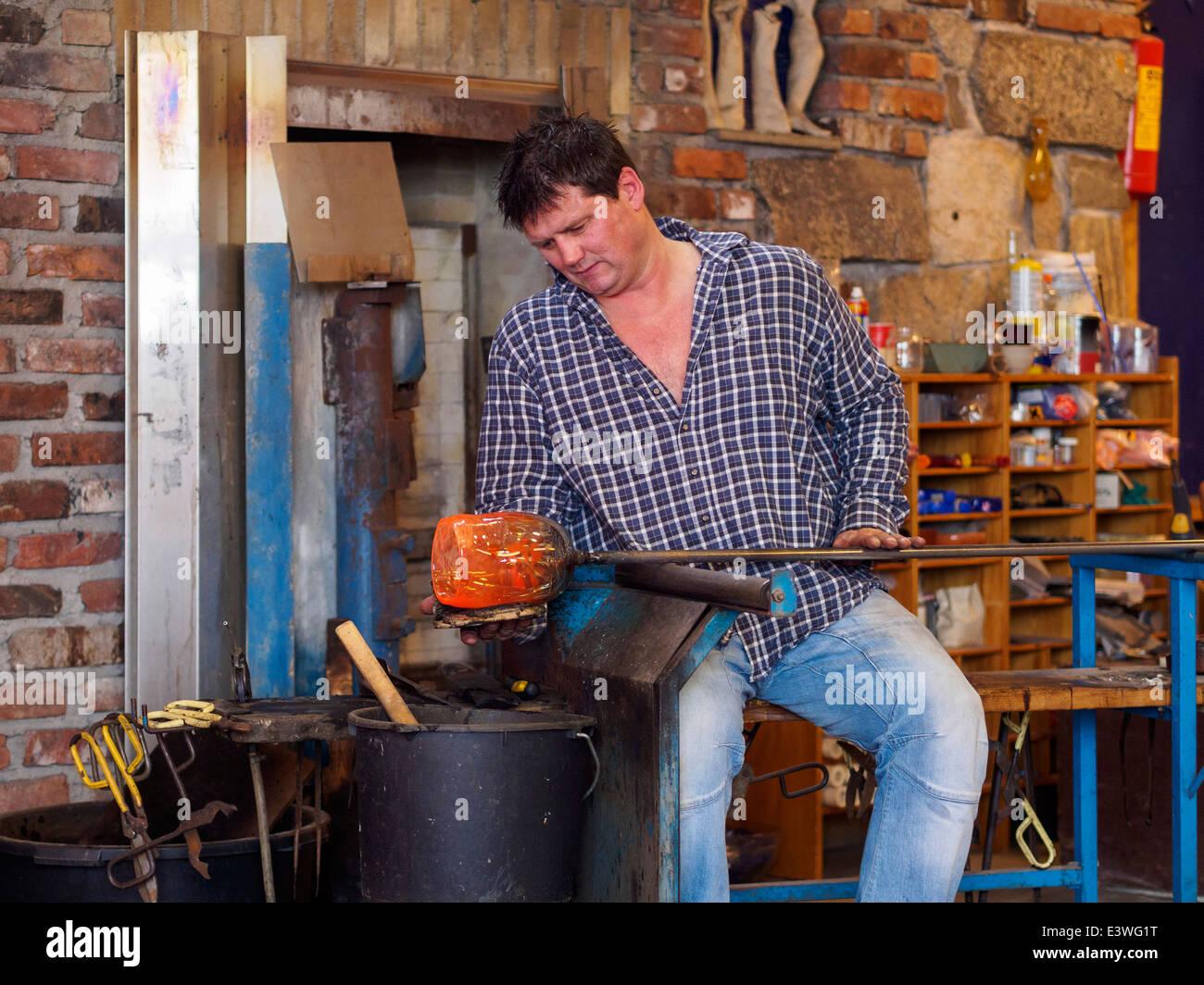 A glassblower works in the Glass Factory Vikten on the Lofoten islands in Norway. - Stock Image
