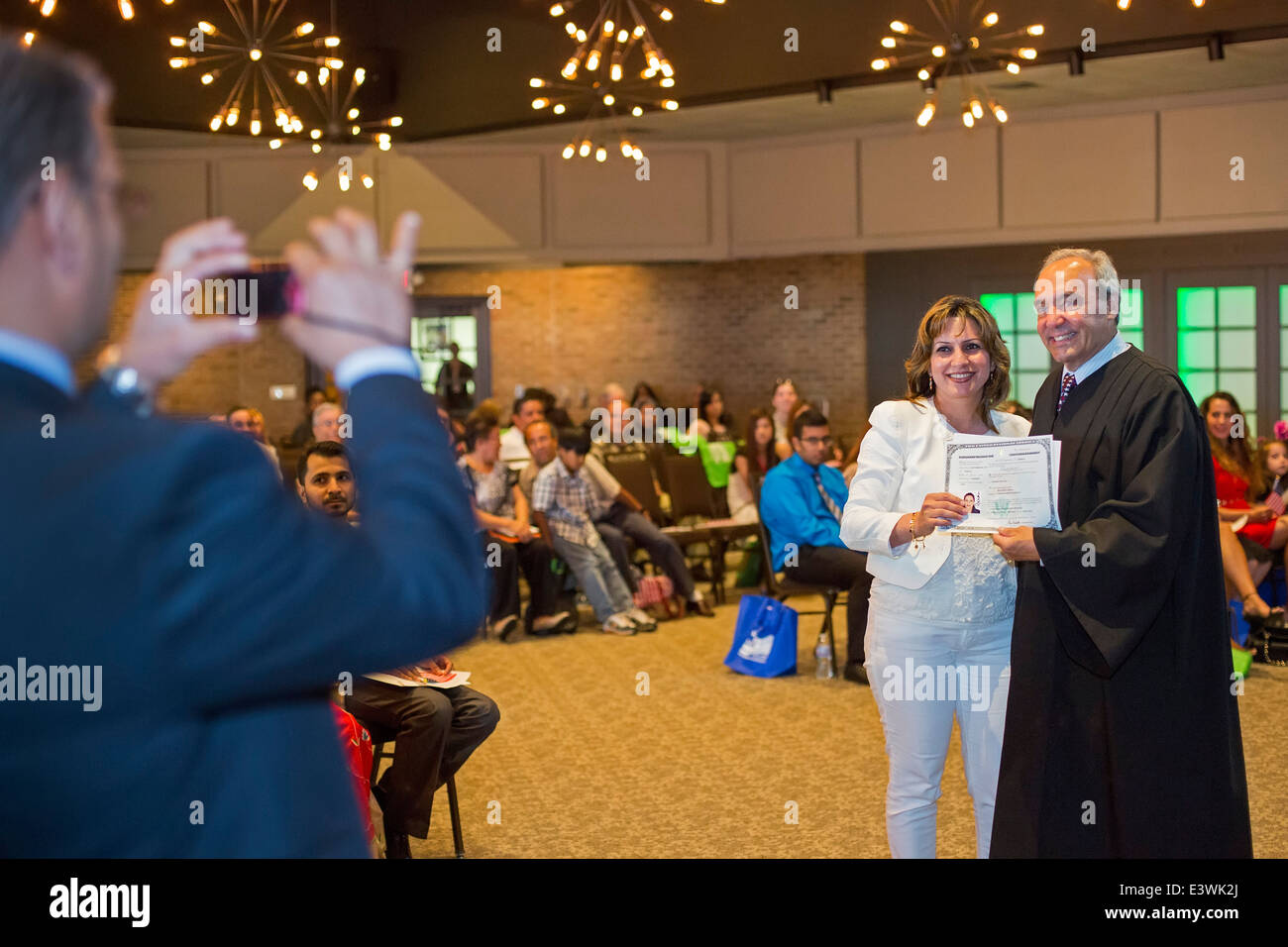 Judge George Caram Steeh, a federal judge, presents a naturalization certificate to a new U.S. citizen. - Stock Image