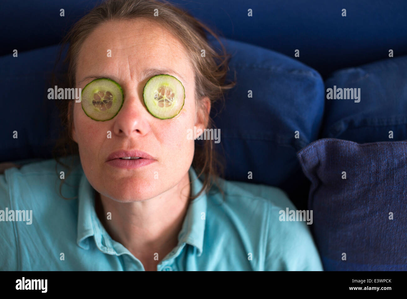 woman suffering from hayfever with cucumber slices on her eyelids - Stock Image