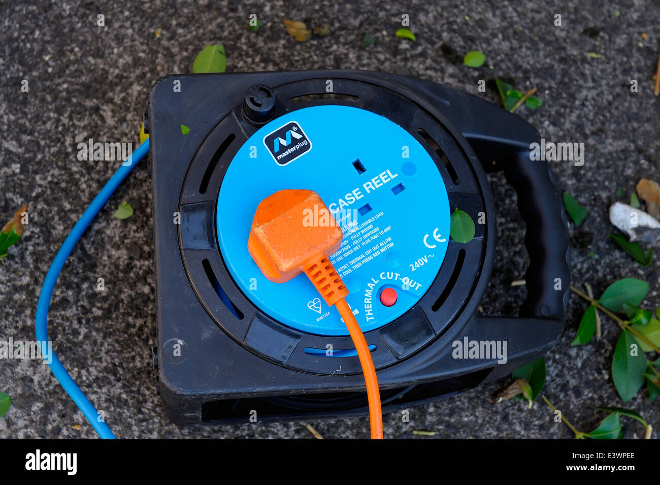 An orange plug lead plugged into a blue extension cable reel - Stock Image