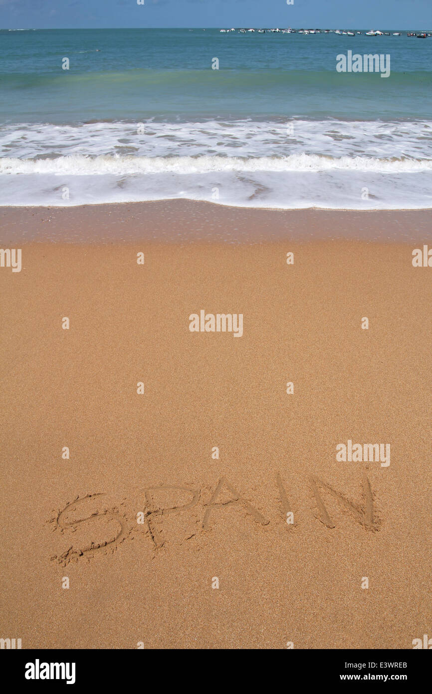 Beautiful beach with Spain word written in sand - Stock Image
