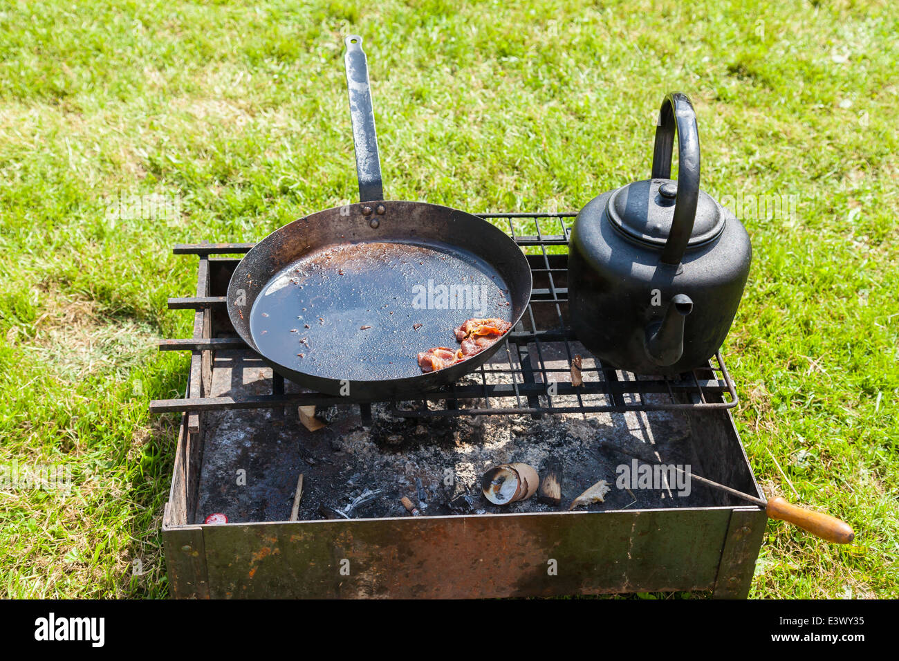 Outdoor fire pit box, with burnt wood embers and eggshells, A Kettle &  Frying pan with cold fat and bacon, sitting on top - Outdoor Fire Pit Box, With Burnt Wood Embers And Eggshells, A Kettle