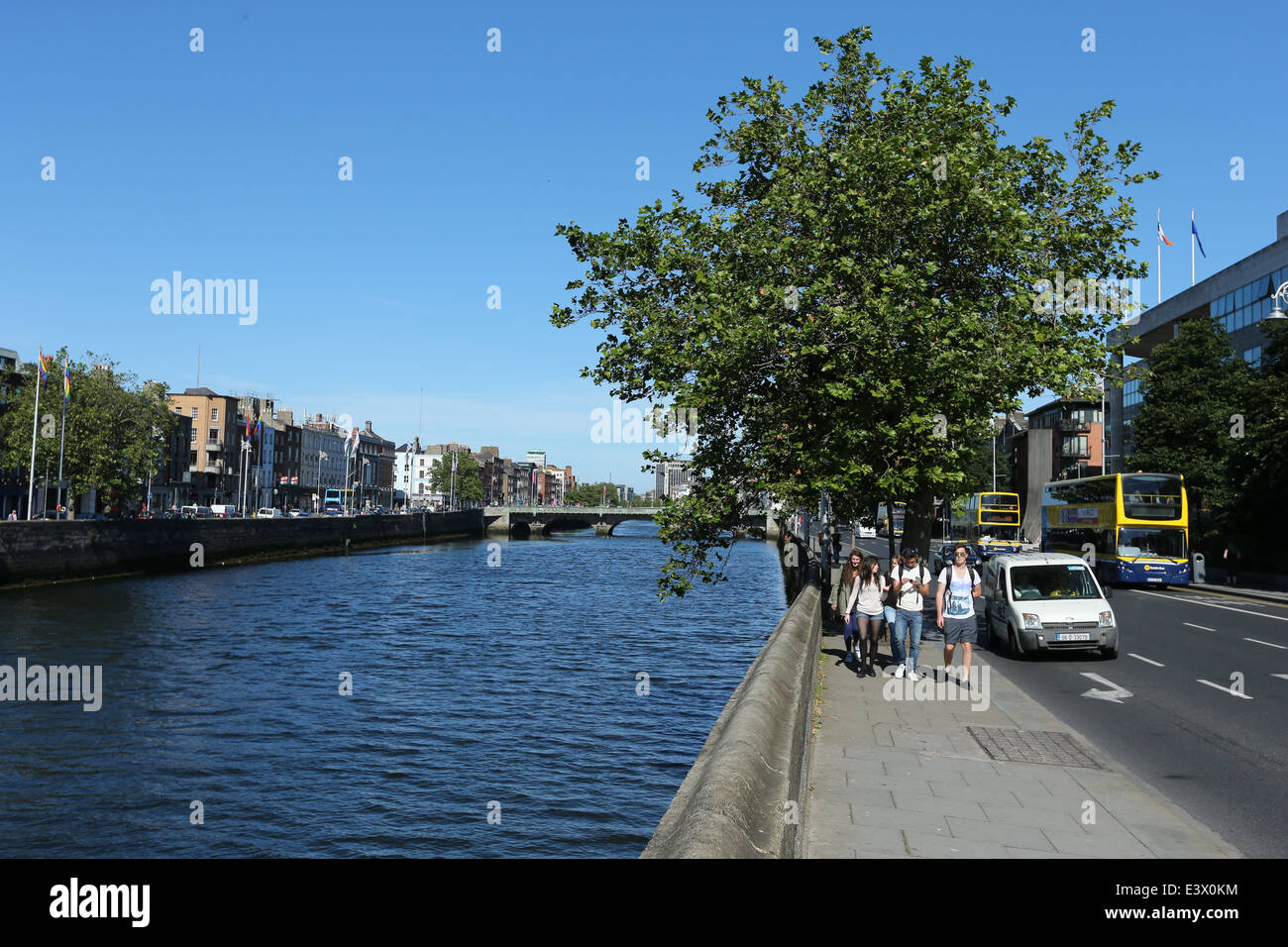 People walk on a footpath at Wood Quay along the River Liffey in Dublin during a period of good weather - Stock Image