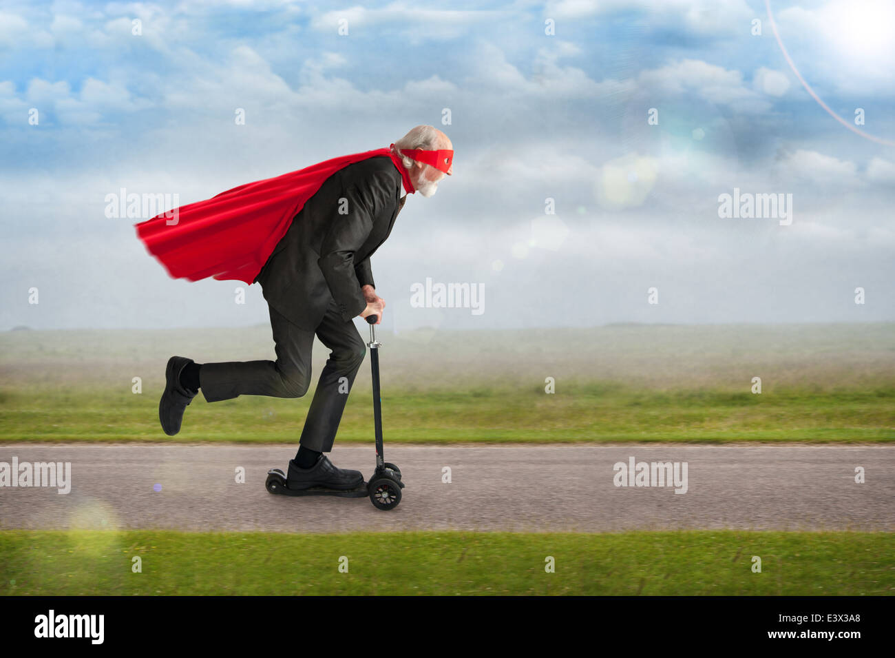 senior superhero man riding a scooter wearing a red cape and mask - Stock Image